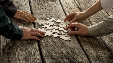 Mehrere Menschen puzzeln auf einem Holztisch.