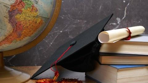 Das Foto zeigt verschiedene Gegenstände, die nebeneinander auf einem Tisch liegen. Unter anderem erkennt man einen Globus, einen Doktorhut, ein Diplom und mehrere Bücher.