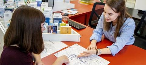Foto eines Lageplans, auf dem eine Frau einer anderen etwas zeigt
