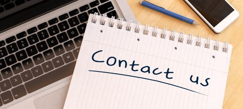 Contact us - handwritten text in a notebook on a desk