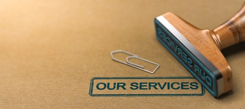 Rubber stamp with the text our services over brown paper background