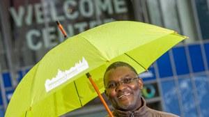 Internationaler Gastwissenschaftler mit grünem Regenschirm vor dem Welcome Center