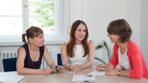 eine Mitarbeiterin der Graduiertenakademie berät zwei Doktorandinnen