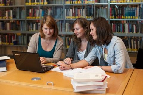 drei Doktorandinnen arbeiten in der Bibliothek