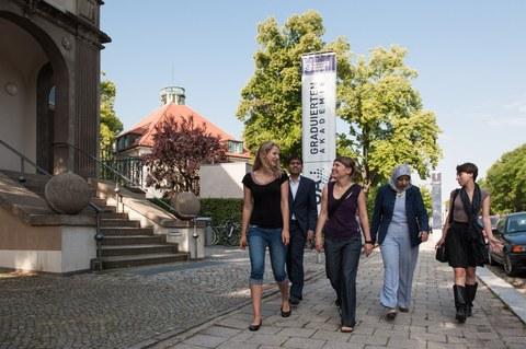 Mitglieder laufen am Gebäude der Graduiertenakademie vorbei