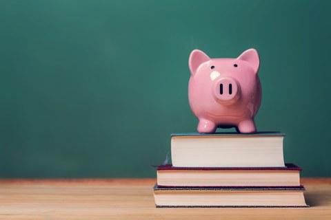 Sparschwein auf einem Bücherstapel