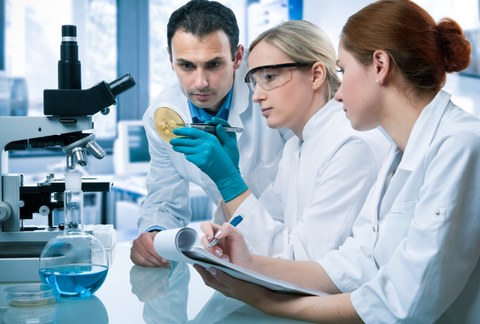 Two female and one male scientist examining a Petri dish in the laboratory.