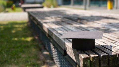 ein Doktorhut liegt auf einer Holzbank