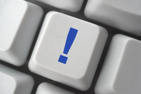 Das Bild zeigt eine Computertastatur. Darauf ist ein blaues Ausrufezeichen abgebildet.