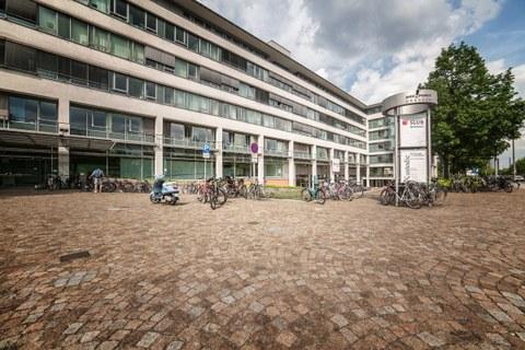 Der Eingang vom Bürogebäude Zellescher Weg. Zu sehen sind die große Fensterfassade des Gebäudes, viele Fahrräder, ein Motorroller, ein Baum und eine Informationssäule.