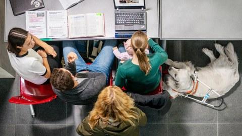 Vier Personen aus der Vogelperspektive aufgenommen. Drei davon sitzen nebeneinander an einem Schreibtisch. Die vierte Person steht hinter ihnen und blickt ebenfalls auf den Schreibtisch. Die rechtssitzende Studentin hält ein Kleinkind auf ihrem Schoß, ihre rechte Hand liegt auf der Braillezeile eines Notebooks, das aufgeklappt auf dem Tisch steht. Rechts von ihr liegt ein Blindenführhund. Auf dem Tisch liegen Bücher, ein Spiralblock, ein zugeklapptes Notebook und Kopfhörer.