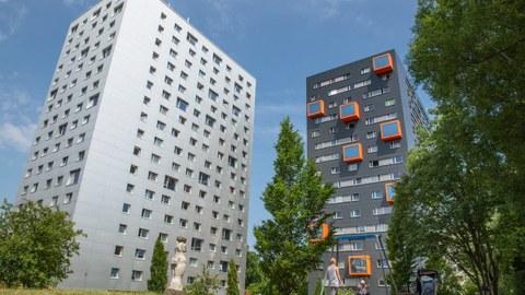 Zwei Wohnheime auf der Hochschulstraße. Zu sehen ist eine Wiese, Bäume, eine Schaukel mit Kind und Frau, ein Kinderwagen und eine Skulptur.