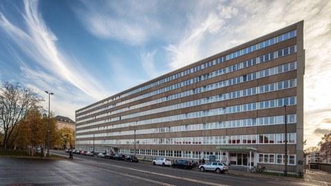 Das Bürogebäude Strehlener Straße mit seiner langen Fensterfront. Es liegt direkt an der Straße. Zu sehen sind viele Fahrräder, Autos, ein Kinderwagen, Bäume und ein wolkenverhangener Himmel.