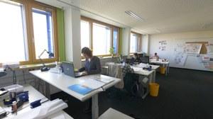 Mitarbeiterinnen und Mitarbeiter von Quabis sitzen in ihrem Büro und arbeiten.