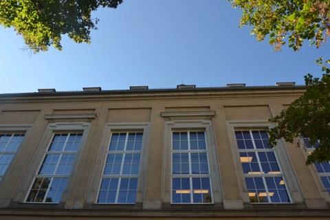 Vier große Fenster des Weberbaus. Durch sie sieht man Lampen an der Decke.