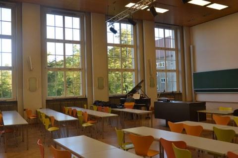 Ein großer Vorlesungssaal im Weberbau. Ein Mann sitzt an einem Klavier und spielt.