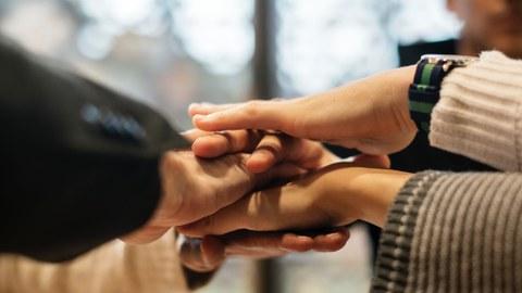 Hände übereinander Team