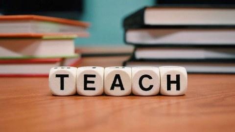 Buchstabenwürfel zeigen das Wort Teach