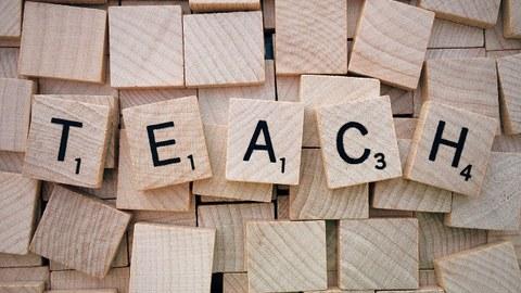 Buchstabenblättchen zeigen das Wort Teach