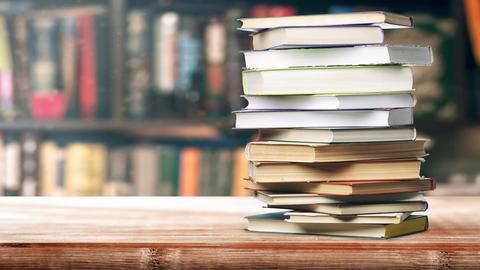Foto: Ein Bücherstapel liegt auf einem Tisch. Im Hintrgrund ist ein Bücherregal.