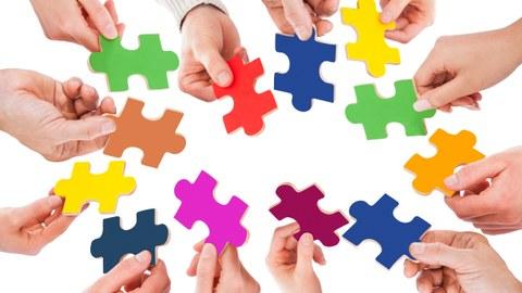 Foto von vielen Händen, die unterschiedliche farbige Puzzleteile in den Händen halten und einen Kreis bilden