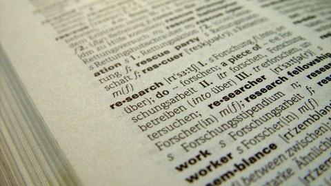 """Bild eines aufgeschlagenen Englisch-Deutsch Wörterbuches. Das englische Wort """"research"""" und seine Übersetzung """"Forschung"""" sind scharfgestellt."""