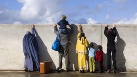 Menschen, die wahrscheinlich geflüchtet sind, schauen über eine Mauer