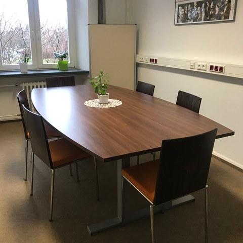 Abgebildet ist der Raum mit einem Tisch in der Mitte und 6 Stühlen.
