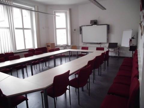 Abgebildet ist der Raum mit Tischen und Stühlen sowie der interaktiven Tafel.