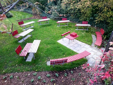 Abgebildet sind wetterbeständige Tische und Bänke für ca. 30 Personen sowie eine Projektionstafel im Freien auf der Wiese hinter dem Fakultätsgebäude.