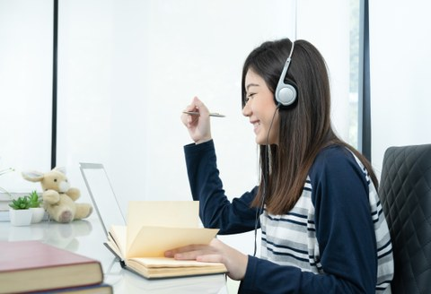 The photo shows a young woman at her desk. She's wearing headphones, smiling, and writing something down in her notebook.