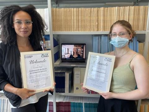 Ayanda Rogge und Alina Päßler halten die Urkunden ins Bild, im Hintergrund sieht man einen Laptop, über den sich Anna Sophie Kümpel zugeschalten hat.