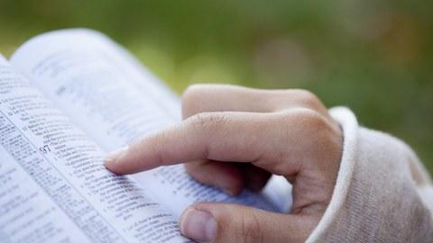 Foto eines aufgeschlagenen Buches, in dem eine Person mit dem Finger liest