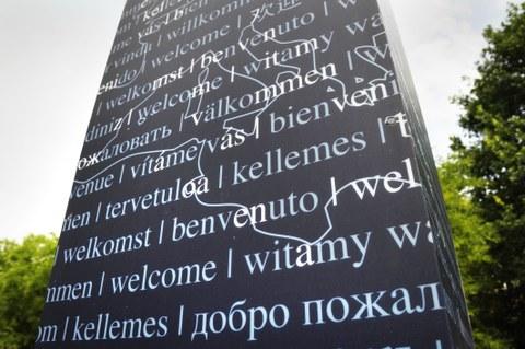 Foto einer Textsäule, auf der sich der Gruß Willkommen in verschiedenen Sprachen befindet