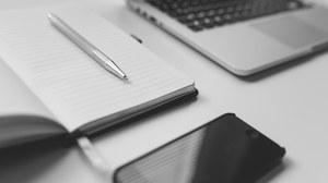 Auf dem Bild sind ein aufgeklappter Notizblock mit Stift, ein Notebook und ein Smartphone zu sehen.