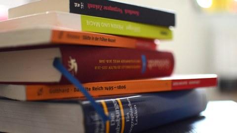Zu sehen ist ein Stapel mit Büchern über Themen aus der Frühen Neuzeit.