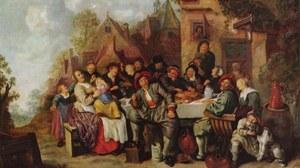 Dargestellt ist eine fröhliche Gesellschaft, die um einen Tisch herum vor einem Wirtshaus sitzt.