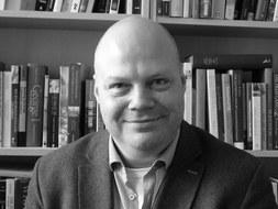 Porträt von Dr. Andrew Wells vor einem Bücherregal