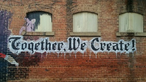 "Logo ""Together We Create"" auf Hauswand"