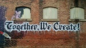 "Logo ""Together We Create"" auf Hauswand"