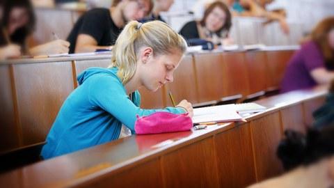 Studentin schreibt eine Prüfung im Hörsaal