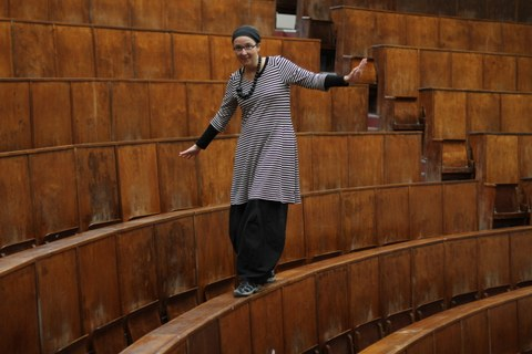 Anja Besand balanciert im Hörsaal auf den Tischen
