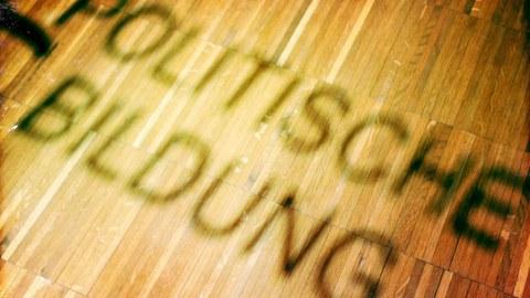 """das Bild zeigt einen Schatten in Form der Buchstaben """"politische Bildung"""
