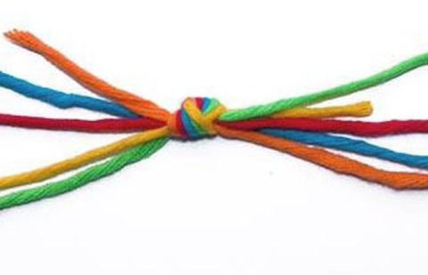 bunte Fäden werden an einer Stelle zu einem Knoten zusammengefasst