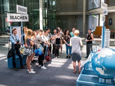 Eine Gruppe geht durch die Ausstellung Frieden Machen