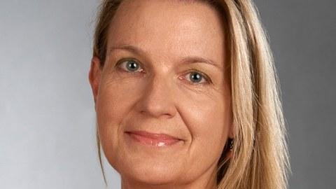 Portraitfoto von Frau Kneuer, helle längere Haare, oranger Blazer, Sie lächelt