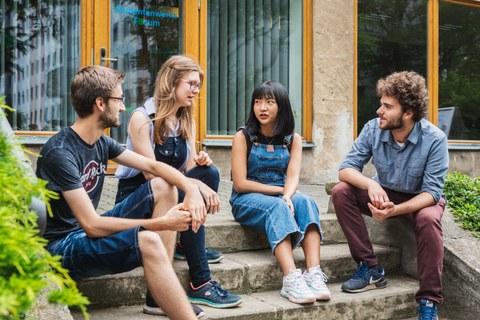Foto: Im Freien sitzen vier Studierende auf einer Treppe und unterhalten sich.