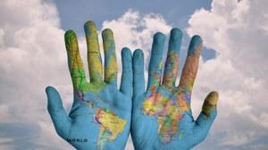 Hände vor Himmel, Hände als Weltkarte bemalt