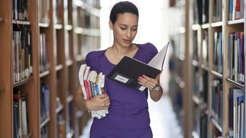 Frau, die Bücher in einer Hand hält und in anderer Buch, in dem sie liest