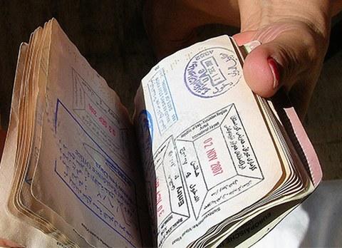 Zu sehen ist eine Hand, die einen Pass mit allerlei Visastempeln durchblättert.